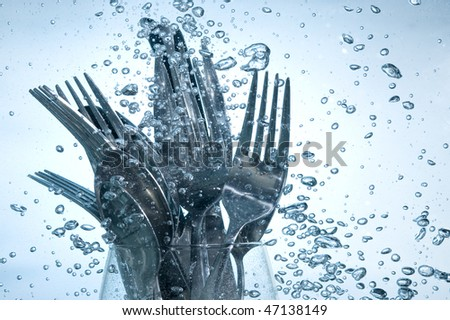 Washing kitchen ware in clear water on bubbles background - stock photo