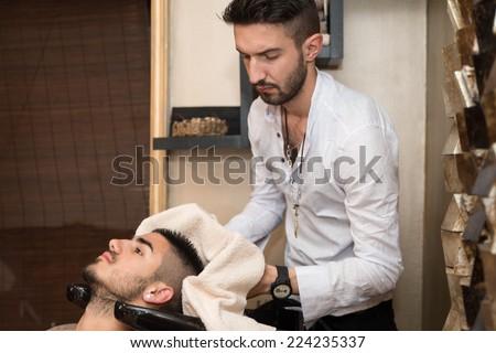 Washing Man Hair In Beauty Parlour Hairdressing Salon - Hairstylist Hairdresser Washing Customer Hair - Young Man Relaxing In Hairdressing Beauty Salon - stock photo