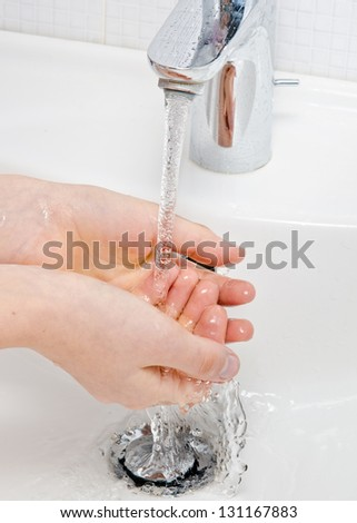 Washing of hands with soap under running water - stock photo