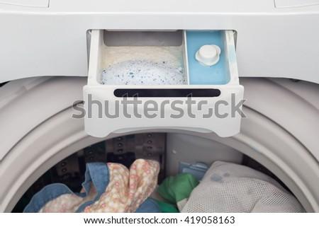 washing powder and fabric softener in washing machine - stock photo