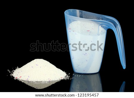 washing powder in a measuring cup, isolated on black - stock photo