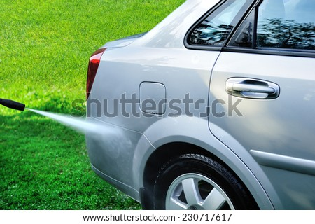 Washing the car a jet of pure water on a background of green water.clean auto. - stock photo
