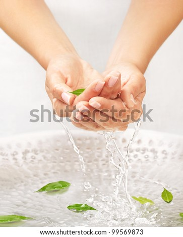 Washing women's hands with splashing and drops over the sink with water and green leaves - stock photo