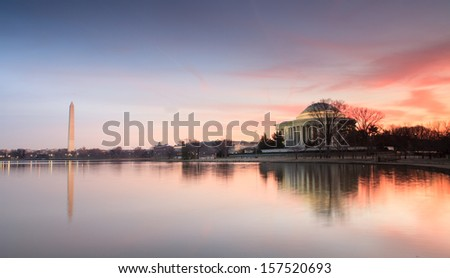 Washington and Jefferson monuments reflecting in the water of the Tidal Basin in Washington, DC at sunrise. - stock photo