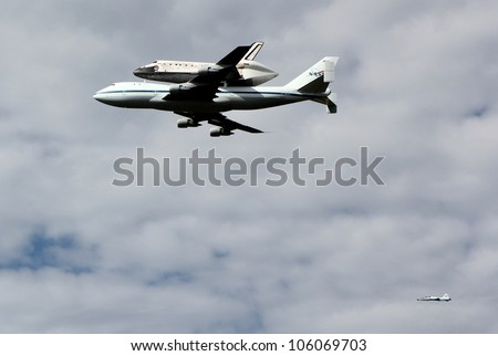 WASHINGTON, D.C.- APRIL 17: Space Shuttle Discovery on top of a Boeing 747, escorted by a Northrop T-38 chase plane, en route to Dulles Airport in Washington D.C. on April 17, 2012. - stock photo