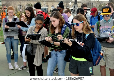 Washington, DC - April 9, 2014:   A group of students on a school field trip taking notes while standing in the plaza of the Grant Memorial near the National Mall - stock photo