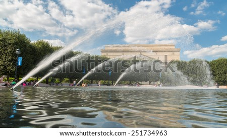 Washington DC - Aug 26: Tourists and residents of Washington DC cool off at the fountain in front of the Archives of the United States of America building on August 26, 2014, Washington DC, USA - stock photo