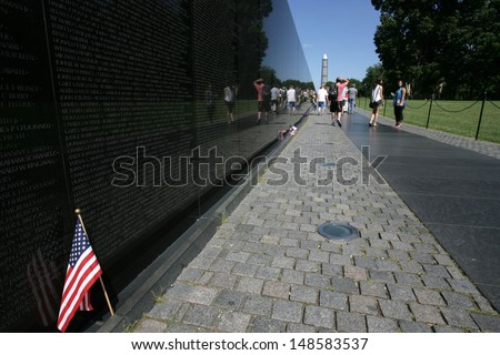 WASHINGTON, DC - JULY 29: An American flag is shown against the Vietnam Memorial on July 29, 2013 in Washington. The memorial honors U.S. service members who fought in the Vietnam War. - stock photo