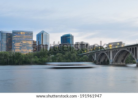 Washington DC - Key Bridge, Rosslyn and tourist boat in Potomac River in the eveniing - stock photo