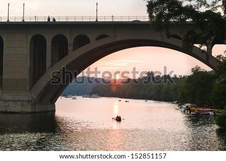 Washington DC - Key Bridge silhouette with kayaking people in Potomac River - stock photo