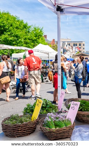 WASHINGTON DC - MAY 24, 2015: Farmers market in the Dupont Circle neighborhood. Baskets of fresh herbs on display for sale in the foreground, shoppers in the background. - stock photo
