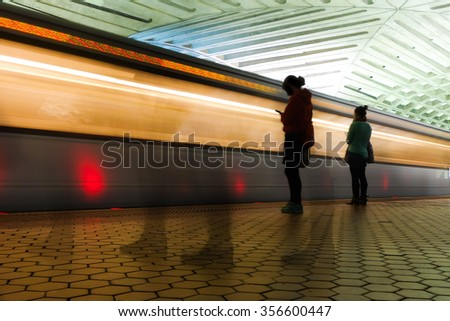 Washington DC Metro station with train and passengers are in motion blur - stock photo