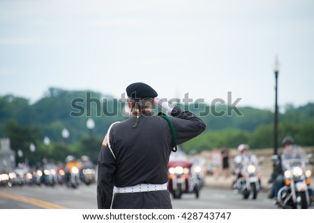 WASHINGTON MAY 29: Air force veteran James Cloye salutes riders take part in Rolling Thunder, a rally to bring attention to POWs and MIAs of US-involved wars, on May 29, 2016 in Washington, DC.   - stock photo