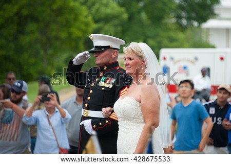 WASHINGTON â?? MAY 29: Staff Sgt. Tim Chambers, known as the saluting marine, stands at attention with his new bride at Rolling Thunder, an annual motorcycle rally, on May 29, 2016 in Washington, DC.   - stock photo