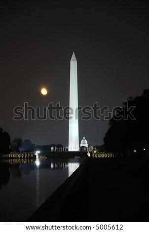 Washington Monument at night with a full orange moon - stock photo