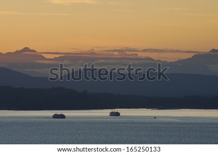 Washington State Ferries and the Olympic Mountains. At sunset, two ferryboats pass each other on their commuter routes from Seattle to Bainbridge Island, Washington. - stock photo
