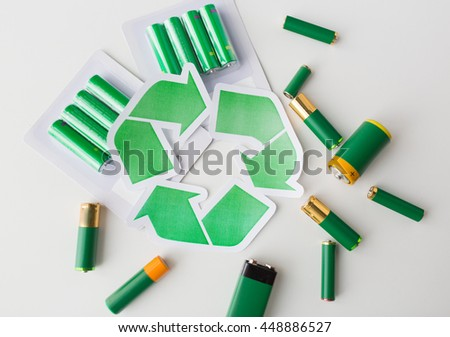 waste recycling, garbage disposal, environment and ecology concept - close up of used alkaline batteries and green recycling symbol - stock photo