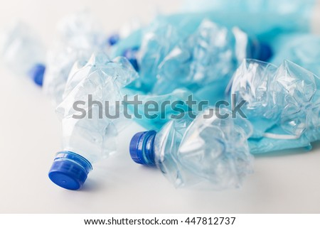 waste recycling, reuse, garbage disposal, environment and ecology concept - close up of empty used crashed plastic water bottles and rubbish bag on table - stock photo