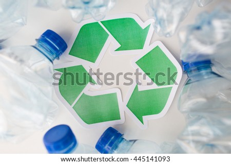 waste recycling, reuse, garbage disposal, environment and ecology concept - close up of used plastic water bottles with green recycle symbol on table - stock photo