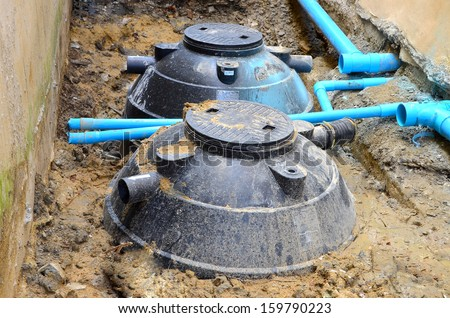 Waste treatment tanks and PVC pipes are installed into the ground.  - stock photo