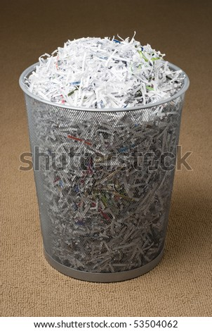wastepaper basket filled with shredded paper on a carpet. - stock photo