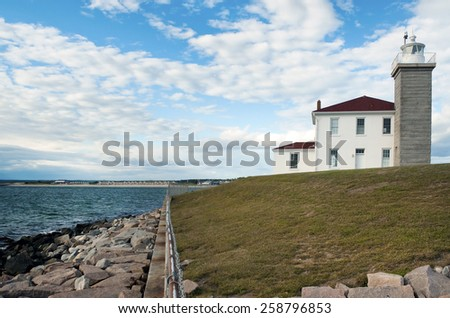 Watch Hill Lighthouse guides mariners along its rocky shoreline in Rhode Island. - stock photo