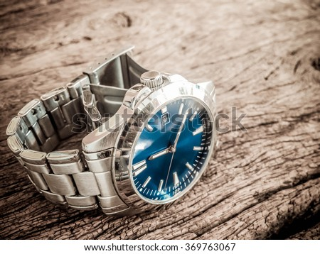 Watch on the old wooden background, vintage style. - stock photo