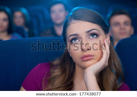 Watching a boring movie. Bored young woman holding hand on chin while watching movie at the cinema - stock photo