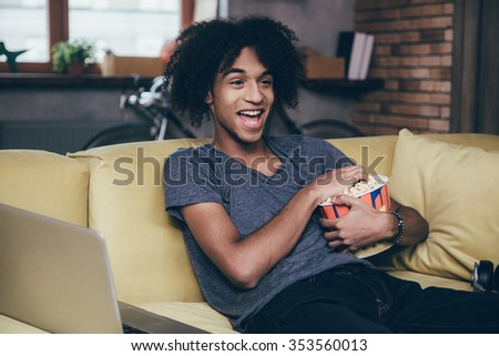 Watching funny movie.  Cheerful young African man watching TV and holding bucket of popcorn while sitting on the couch at home - stock photo