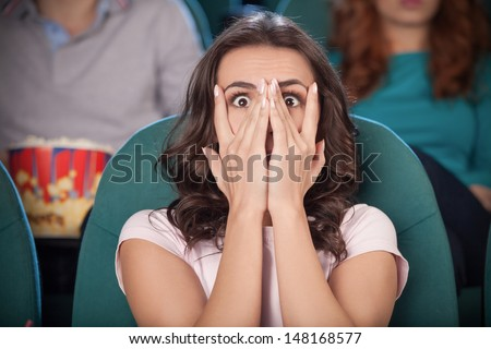 Watching  horror movie. Terrified young women covering her face with hand while watching movie at the cinema - stock photo