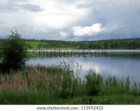 Watching the boat from the shore - stock photo