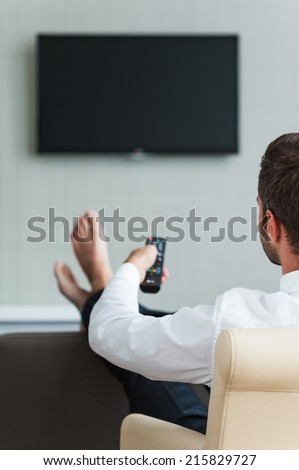 Watching TV in hotel. Rear view of man in white shirt watching TV and holding remote control in hand  - stock photo