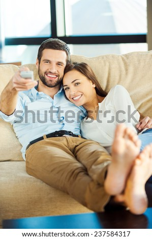 Watching TV together. Beautiful young loving couple sitting together on the couch and watching TV while man holding remote control and smiling  - stock photo