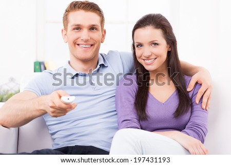 Watching TV together. Cheerful young man and woman watching TV while sitting together on the couch - stock photo