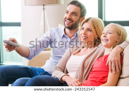 Watching TV together. Happy family of three bonding to each other and smiling while sitting on the couch and watching TV together - stock photo