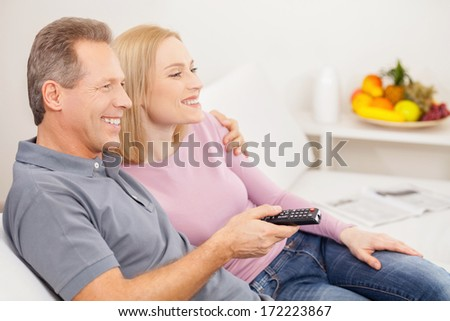 Watching TV together. Side view of cheerful mature couple sitting together and watching TV - stock photo