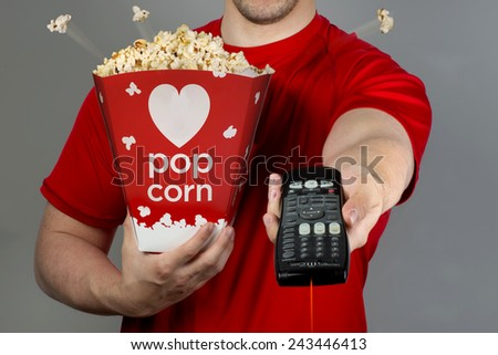 Watching TV with remote control and pop corn. - stock photo