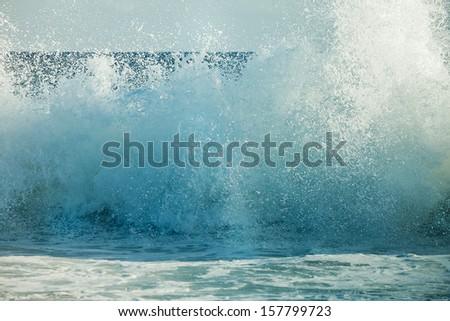 Water and droplets explode closeup as a big breaker hits the shore on sunny day in Florida. - stock photo