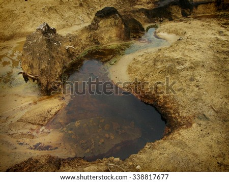 Water and soil contaminated by chronic carcinogenic crude oil pollution at an illegal oil field in East Java, Indonesia. - stock photo