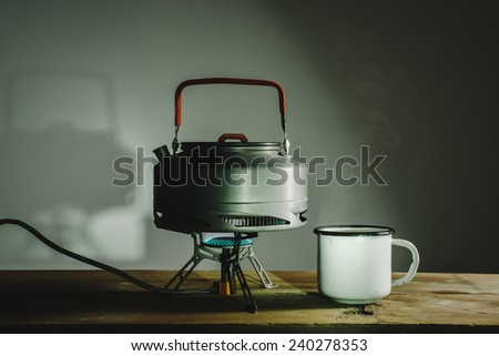 water boils in a cup on a gas burner camp - stock photo