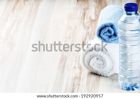 Water bottle and towels. Fitness concept - stock photo