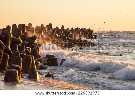 Water breaker with waves and water splashes on Baltic sea while sunset with seagulls - stock photo