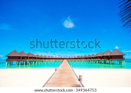 Water bungalows and wooden jetty on tropical island in Indian Ocean - stock photo
