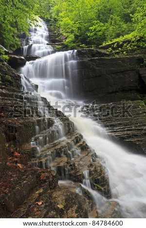 Water cascades over layers of rock and dead leaves at Lye Brook Falls near Manchester, Vermont, the tallest waterfall in Vermont. - stock photo