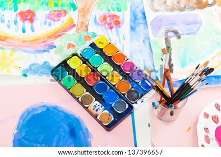 Water colors and brushes with paintings - stock photo