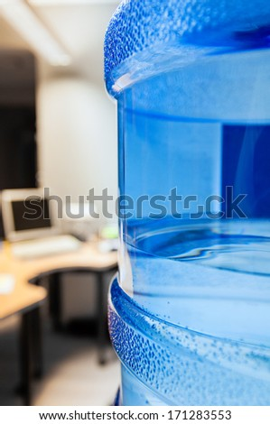 Water cooler with fresh water as seen in a modern office with computers in the background - stock photo