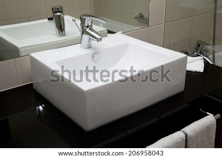 Water crane and white sink in a bathroom - stock photo