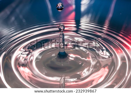 Water drop and concentric waves with column of water that rise again with blue and red light background - stock photo