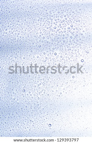 Water drop and droplet on mirror bright white and blue background - stock photo