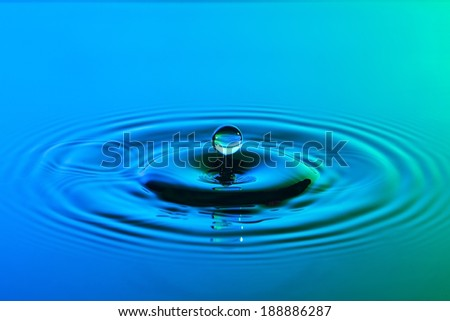 Water drop close up with concentric ripples on colourful blue and green surface - stock photo